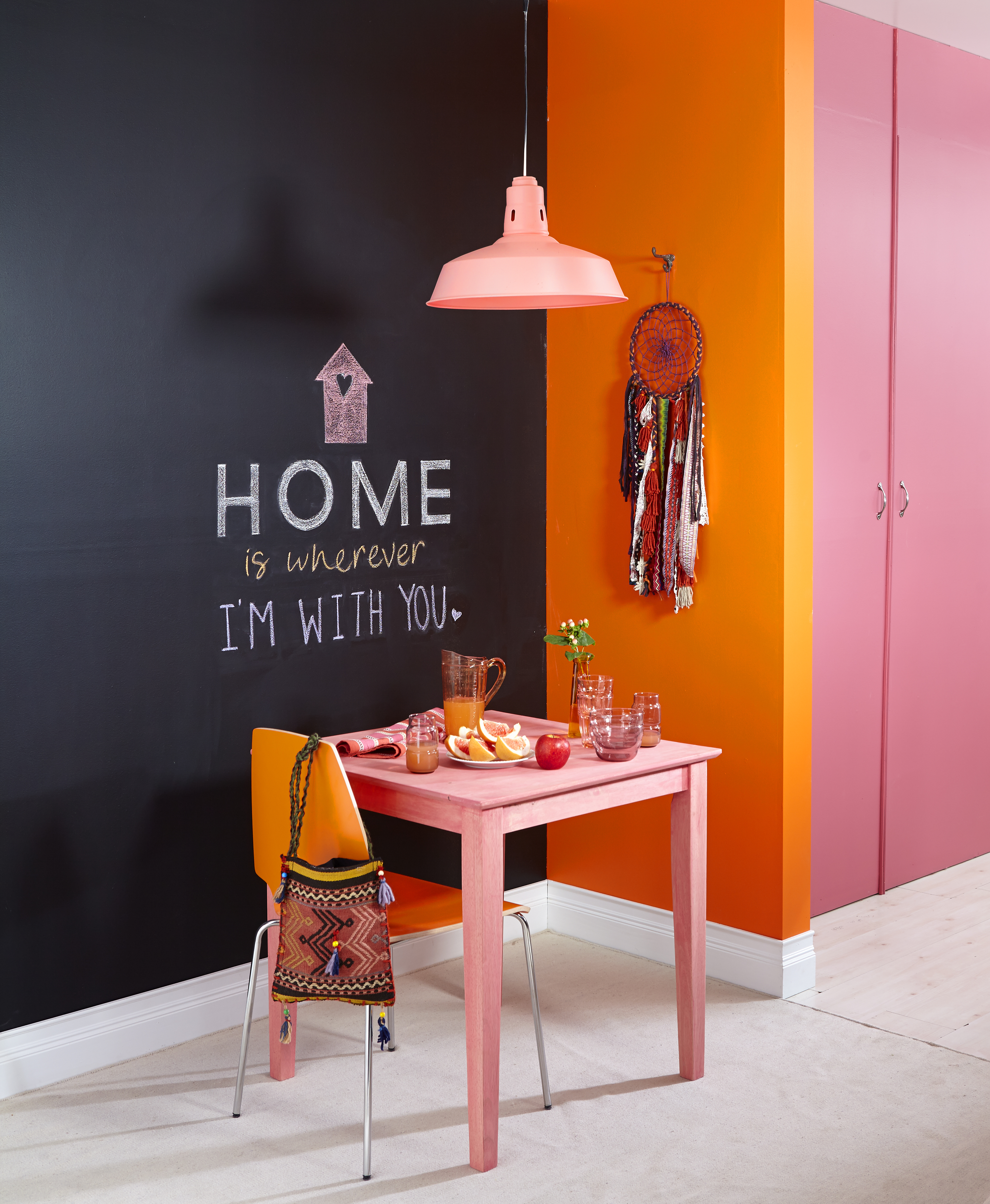 pink table and lamp with orange wall